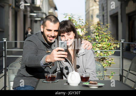 Young couple sitting outside cafe, taking selfie, using smartphone - Stock Photo