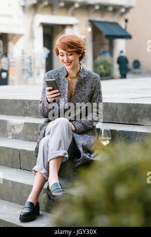 Young woman sitting on steps, using smartphone, glass of wine beside her - Stock Photo
