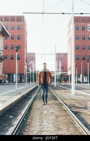 Cool young bearded man walking along city tram lines - Stock Photo