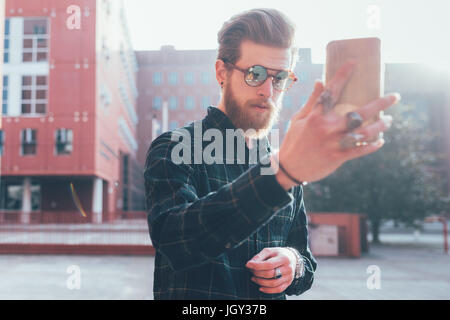 Cool young male hipster taking smartphone selfie in city - Stock Photo