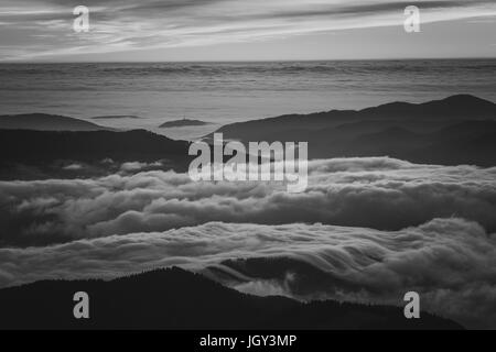 A river of fog over the valleys of Ceahlau National Park - Stock Photo