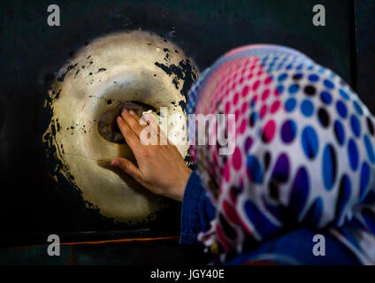 A tourist places her fingers in the wishing column and rotates her hand in Hagia Sophia, Sultanahmet, istanbul, - Stock Photo