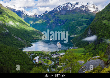 High view over Geirangerfjorden surrounded by snowcapped mountains in summer. Geiranger, Sunnmøre, Møre og Romsdal - Stock Photo