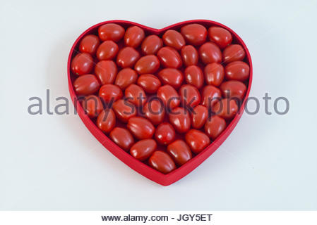 Cherry tomatoes in heart shaped plate against white background - Stock Photo