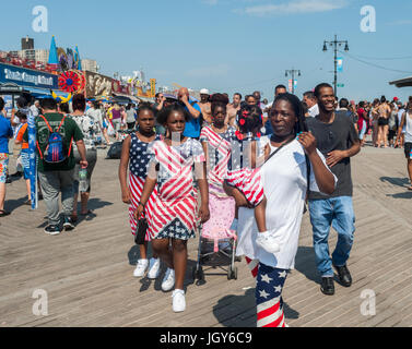 A patriotically dressed family promenades on the boardwalk in Coney Island in Brooklyn in New York  on Independence - Stock Photo