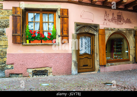 Ornate window and wooden shutters decorated with colorful fresh flowers in Colmar, France, Europe - Stock Photo