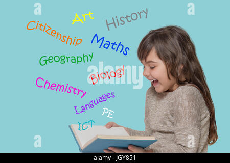 Laughing long haired little girl is holding a book, from which the names of the school subjects fly out. - Stock Photo