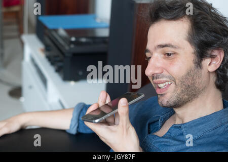 Man talking on the phone with digital voice assistant - Stock Photo