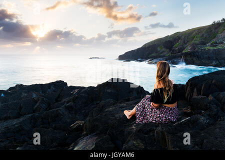 A beautiful bohemian-styled girl sits on a rocky headland and watches the morning sun burst above the clouds during - Stock Photo