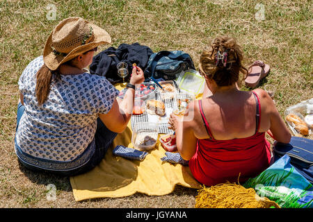 Two Women Sitting On The Banks Of The River Ouse Enjoying A Picnic, Lewes, Sussex, UK - Stock Photo