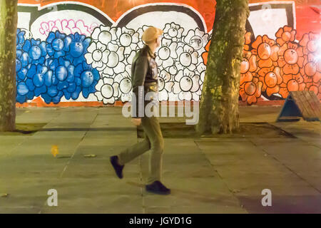 parisian walking in front painting flowers in blue white red Homage at the victims of the terrorist attacks in Paris - Stock Photo