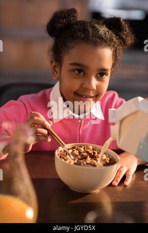 portrait of smiling little girl having breakfast at home - Stock Photo