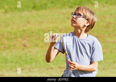 Child playing outdoors in a park with arrow helicopter elastic rocket toy - Stock Photo