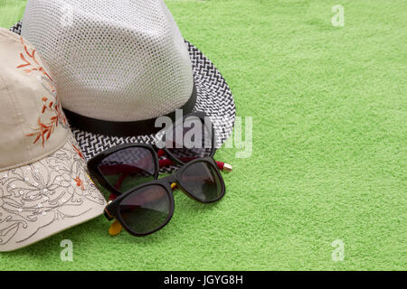 Two beach hats and two pairs of glasses on a green background - Stock Photo