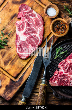 Raw marbled beef steaks on wooden cutting board. Top view - Stock Photo