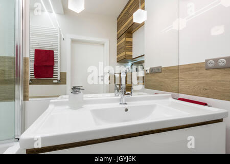 White sink in modern bathroom with wooden finish - Stock Photo