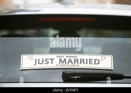 A Just Married sign on the back window of a car. - Stock Photo