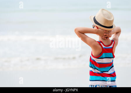Boy in a hat and sunglasses admiring the sea - Stock Photo