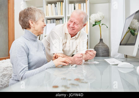 Senior couple of retirees  doing accounting at home - Stock Photo
