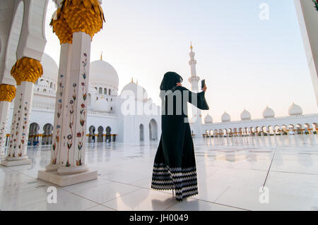 Emirati woman taking a selfie at the Sheikh Zayed Grand Mosque in Abu Dhabi, UAE - Stock Photo