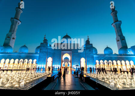 Emirati woman in traditional black dress taking a selfie at the Sheikh Zayed Grand Mosque in Abu Dhabi, UAE - Stock Photo
