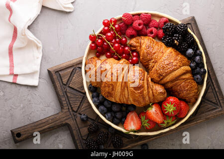 Healthy breakfast with freshly baked croissants and berries - Stock Photo