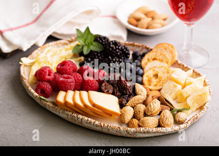 Cheese plate with nuts and berries - Stock Photo