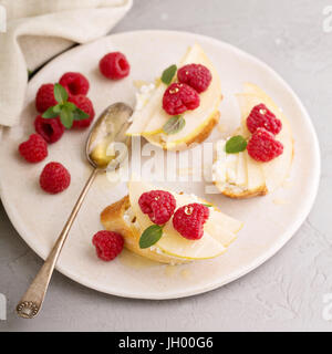 Open faced sandwiches with cheese, pears and raspberry - Stock Photo