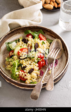 Warm salad with bulgur, vegetables and leaves - Stock Photo