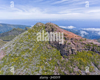 Aerial view of the highest mountain peak in Madeira island, Pico Ruivo, with walkers on a hiking trail to the top - Stock Photo