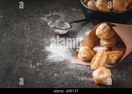 Homemade baking, puff pastries. Trendy food. Cronuts popcorn, puff donuts holes, in a black bowl and a paper bag, - Stock Photo