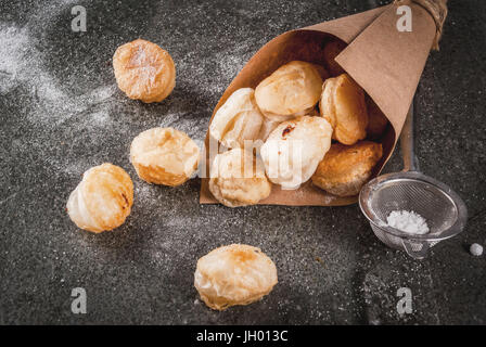 Homemade baking, puff pastries. Trendy food. Cronuts popcorn, puff donuts holes, in paper bag, with powdered sugar. - Stock Photo