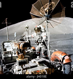 Astronaut Eugene A. Cernan, Apollo 17 commander, approaches the parked Lunar Roving Vehicle (LRV) on the lunar surface - Stock Photo