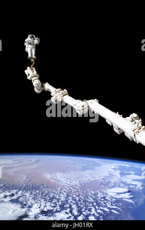 Astronaut Stephen K. Robinson, STS-114 mission specialist, anchored to a foot restraint on the extended International - Stock Photo