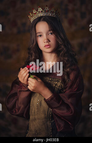 Portrait of cute girl wearing a crown with a rose in hands. Young queen or princess - Stock Photo