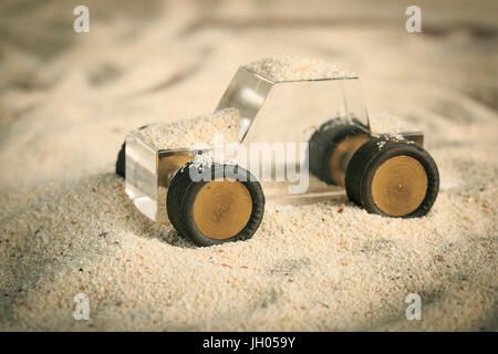 Transparent Methacrylate toy car in the sand - Stock Photo