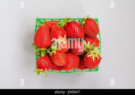 Fresh strawberries in a plastic green punnet on a light grey background - Stock Photo