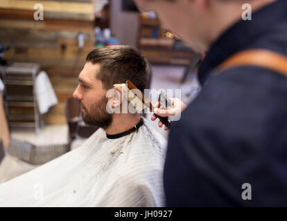 man and barber with brush cleaning hair at salon - Stock Photo
