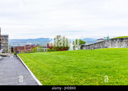 Quebec City, Canada - May 29, 2017: Green grass fields plains in park with fortifications stone wall and cityscape - Stock Photo