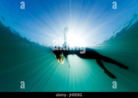 A beautiful woman floats on her back in the ocean as she is surrounded be bright ethereal light and sun rays. - Stock Photo