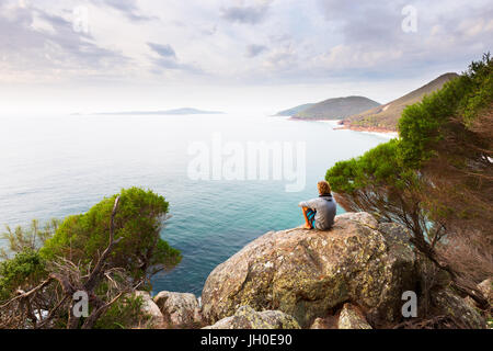A man sits on a boulder overlooking a panoramic view of a beautiful ocean coastline near Newcastle, Australia. - Stock Photo