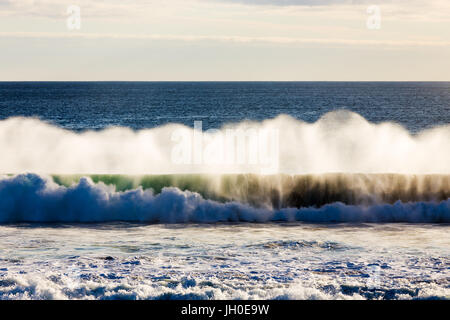 A powerful Southern Ocean wave crashes into shore, as the spray is illuminated in soft evening light on an isolated - Stock Photo