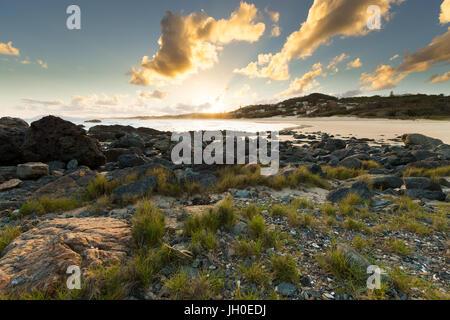 The sun sets on a vibrant beach scene in Port Macquarie, Australia, illuminating the surrounding clouds, coastline - Stock Photo