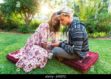 A young couple looking at a phone whilst sitting in a vibrant garden as bright sun light shines through the trees. - Stock Photo