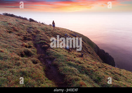 A silhouetted woman walking on a coastal trail, stops to watch a beautiful pink sunrise above the cliff tops near - Stock Photo
