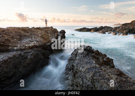 A person watches the sun rise over the ocean in a beautiful rocky seascape scene in Port Macquarie, Australia. - Stock Photo