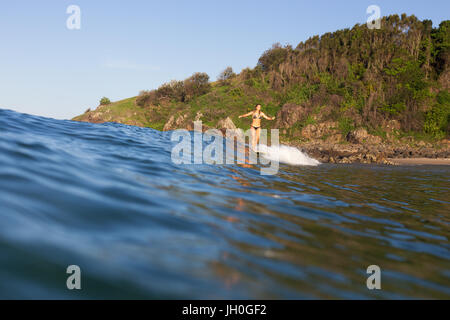 A happy woman rides on the nose of a malibu at an empty surf break near Port Macquarie, Australia. - Stock Photo
