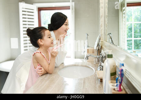 Mother teaching daughter brushing teeth - Stock Photo