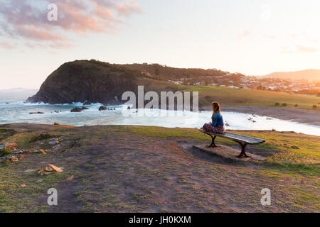 A woman sits on a wooden bench and watches the golden sun light disappearing from the beautiful coastline around - Stock Photo