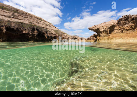 A split shot of a pristine rock pool on an isolated coastline in South Australia. - Stock Photo